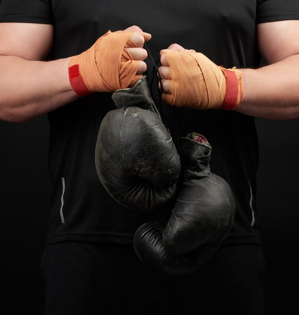 Gespierde atleet in een zwart uniform houdt zeer oude zwarte bokshandschoenen in zijn hand, zijn handen zijn verbonden met een oranje elastisch sportverband Premium Foto