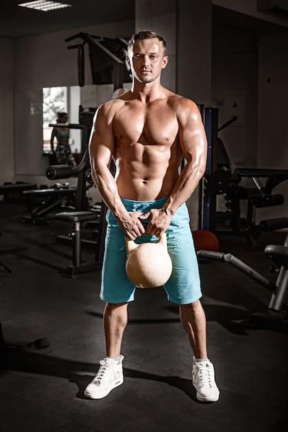Gespierde bodybuilder man doen oefeningen met gewicht in de sportschool Gratis Foto