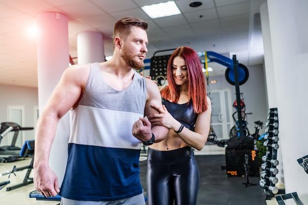 Gespierde bodybuilder toont zijn biceps aan de mooie jonge vrouw in sportcentrum. verbaasd wijfje wat betreft de arm van het mannetje terwijl zich dicht bij de atleet in crossfitgymnastiek bevindt. Premium Foto