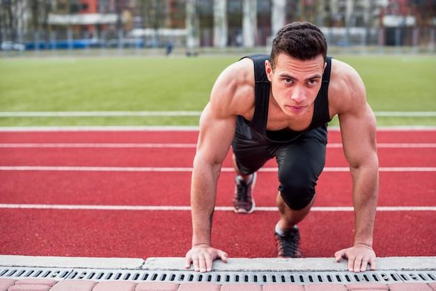 Gespierde fit gezonde jonge man doet pushup op racebaan Gratis Foto