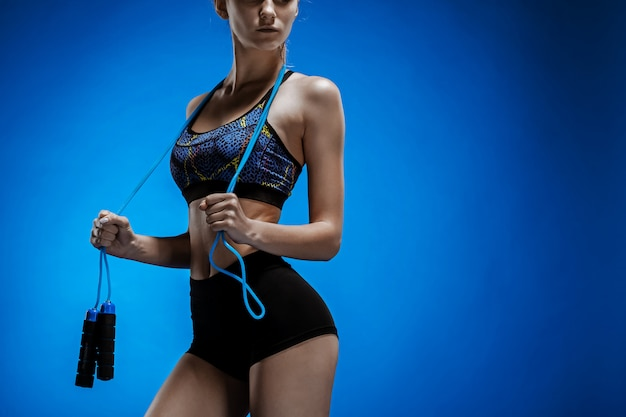 Gespierde jonge atleet met een springtouw op blauw Gratis Foto