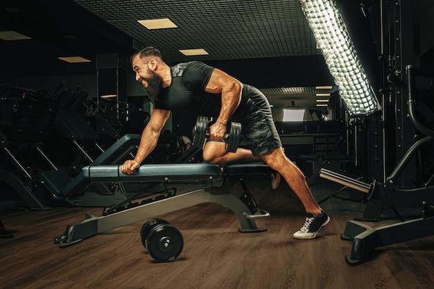 Gespierde jonge man tillen gewichten in een donkere sportschool Premium Foto