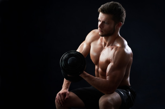 Gespierde jonge man tillen gewichten op zwarte achtergrond Gratis Foto