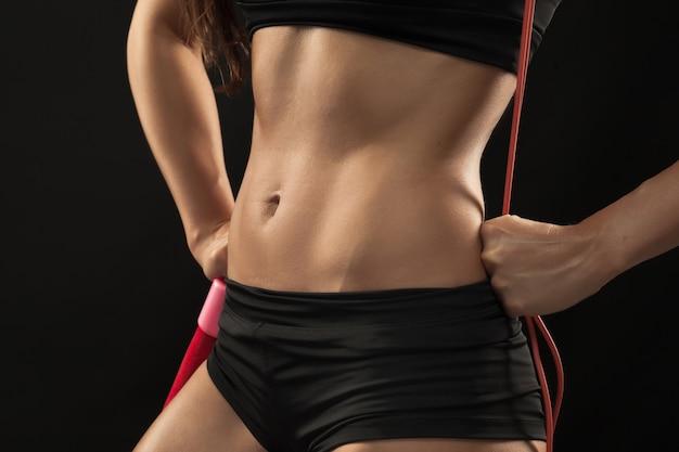 Gespierde jonge vrouw atleet met een springtouw op zwart Gratis Foto