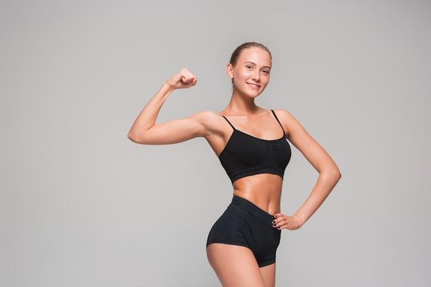 Gespierde jonge vrouw atleet op grijs Gratis Foto