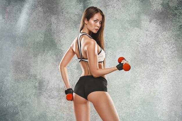 Gespierde jonge vrouw atleet poseren Gratis Foto