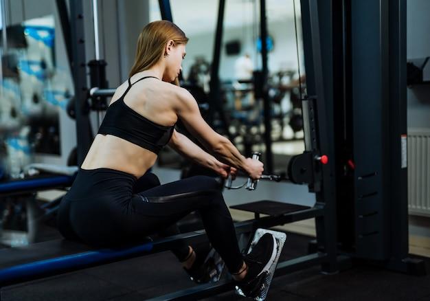 Gespierde jonge vrouw in zwarte sportkleding en trainers doet intensieve training door gewichten te trekken in de sportschool. Premium Foto