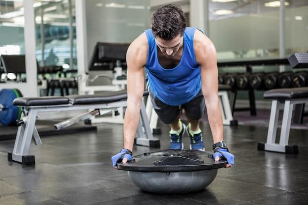 Gespierde man doen push-up met bosu bal in de sportschool Premium Foto