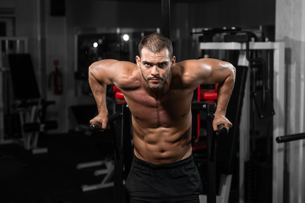 Gespierde man doet push-ups op ongelijke balken in crossfit gym. Premium Foto