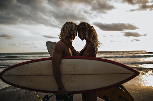 Gespierde man en zijn slanke meisje genieten van elkaar. paar poseren met surfplanken Gratis Foto