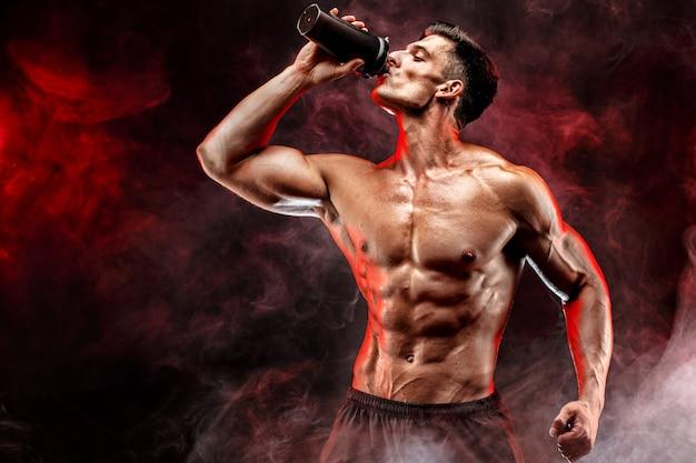 Gespierde man met eiwit drankje in shaker Premium Foto