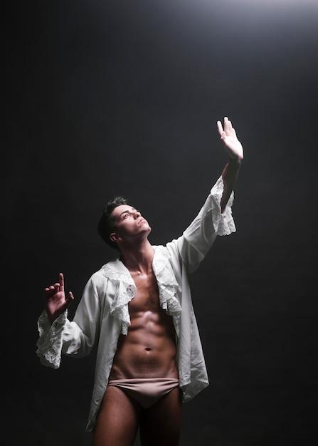 Gespierde man strekt de hand uit naar het licht Gratis Foto