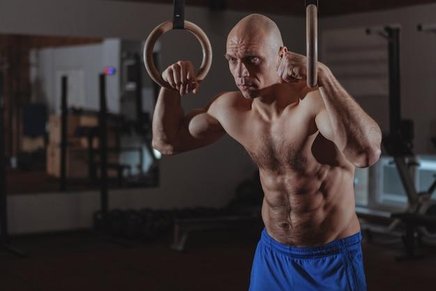 Gespierde mannelijke crossfit atleet trainen op gymnastiek ringen Premium Foto