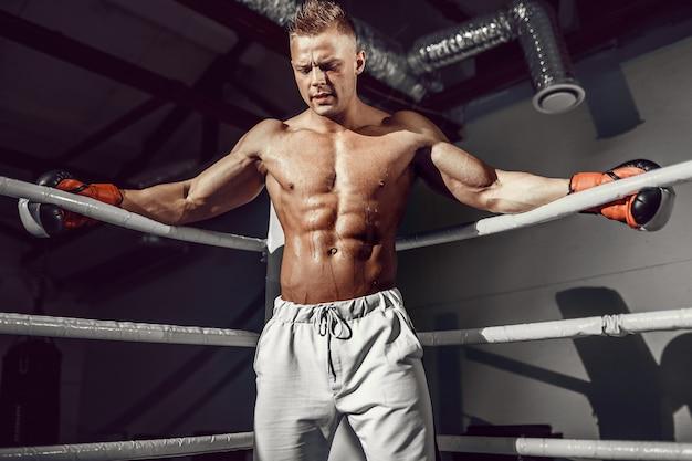Gespierde professionele kickbokser rustend op de touwen in de hoek van de ring tijdens de training voor de volgende wedstrijd Premium Foto