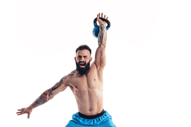 Gespierde shirtless getatoeëerde bebaarde mannelijke atleet bodybuilder training met kettlebell Premium Foto
