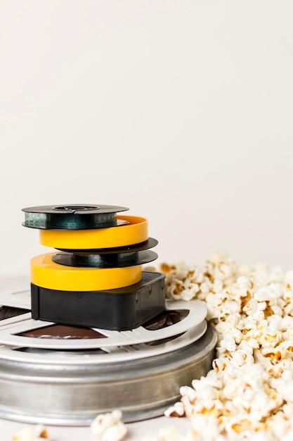 Gestapeld van filmhaspels met popcorns tegen witte achtergrond Gratis Foto