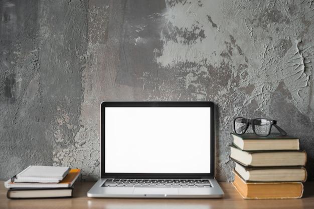 Gestapelde boeken; bril en laptop met leeg wit scherm op houten oppervlak Gratis Foto