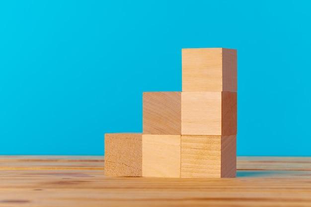 Gestapelde houten blokken op houten bureau tegen blauwe achtergrond Premium Foto