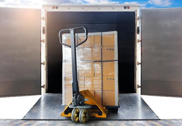 Gestapelde kartonnen dozen op palletrek laden in zeecontainer. vrachtverzendingsdozen, wegvrachtwagen, opslag. logistiek en transport. Premium Foto