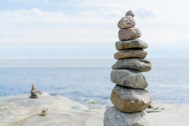 Gestapelde rotsen balanceren, stapelen met precisie. stenen toren aan de kust. kopieer ruimte. Premium Foto