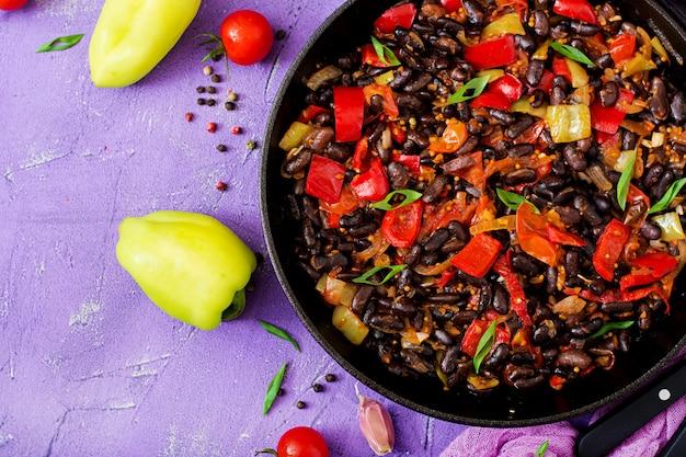 Gestoofde zwarte bonen met paprika en tomaten met pikante saus in een pan. flay lag. bovenaanzicht Premium Foto