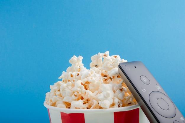 Gestreepte papieren beker met popcorn, afstandsbediening op tv Premium Foto