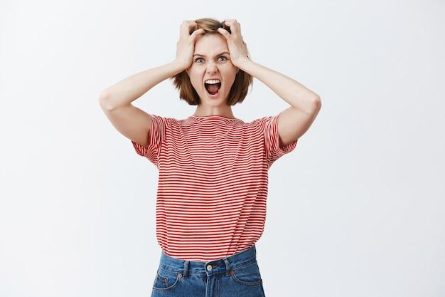 Gestresste en gespannen jonge vrouw grijpt haar hoofd vast en schreeuwt, raakt in paniek over iets, kijkt boos Gratis Foto