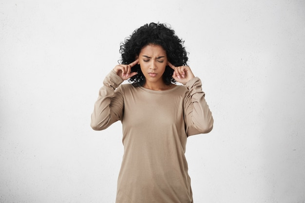 Gestresste gefrustreerde jonge donkere vrouw met een beige top met lange mouwen die haar oren dichtstak Gratis Foto