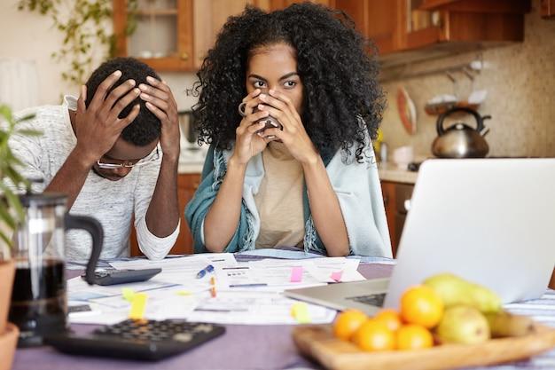 Gestresste werkloze echtgenoot met veel schulden die wanhopig het hoofd vasthoudt omdat hij geen rekeningen kan betalen Gratis Foto