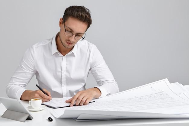 Getalenteerde jonge europese bebaarde hoofdingenieur met ronde bril en wit formeel overhemd zittend op zijn werkplek Gratis Foto