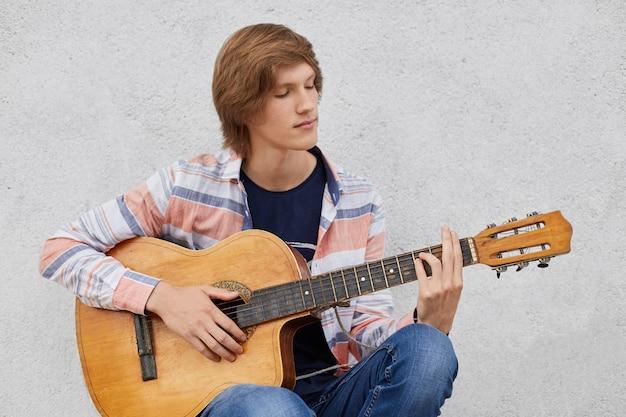 Getalenteerde tiener met trendy kapsel met akoestische gitaar die zijn favoriete liedjes speelt terwijl hij tegen grijze betonnen muur zit Gratis Foto