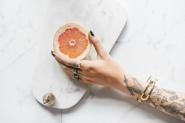 Getatoeã «rde vrouw die een sinaasappel over een marmeren achtergrond houdt Gratis Foto