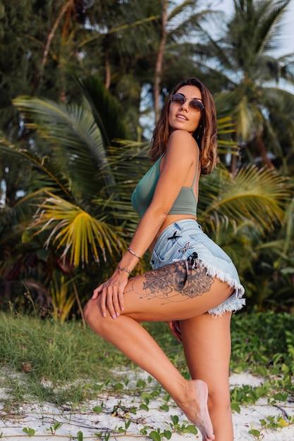 Getatoeëerde blanke vrouw in denim shorts en groene trendy crop top Gratis Foto