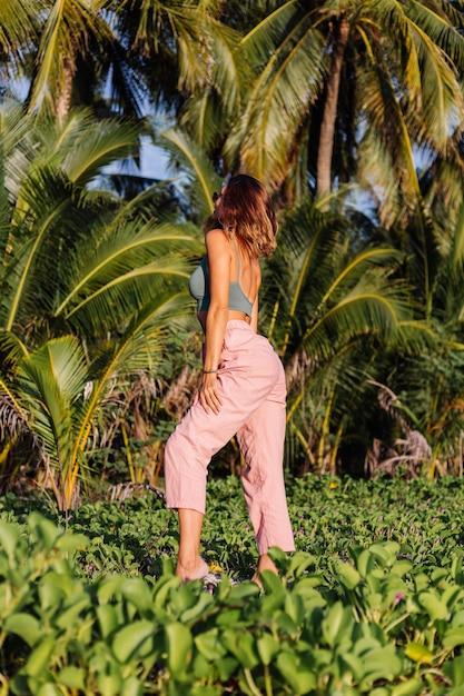 Getatoeëerde blanke vrouw in roze broek en groene trendy crop top Gratis Foto