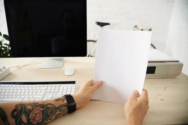 Getatoeëerde handen houden een pak blanco vellen papier vast voordat ze in de lade van de thuisprinter op het werkende bureaublad worden geladen Gratis Foto