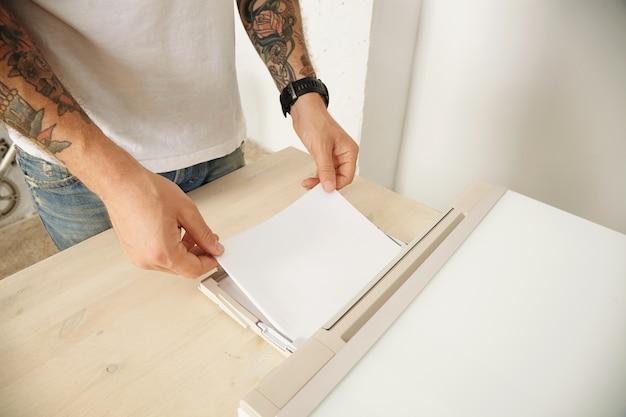 Getatoeëerde handen laden mft-apparaat thuis op met een nieuw pak vellen papier Gratis Foto
