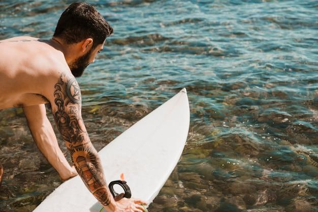 Getatoeëerde man brengen surfplank op water Gratis Foto
