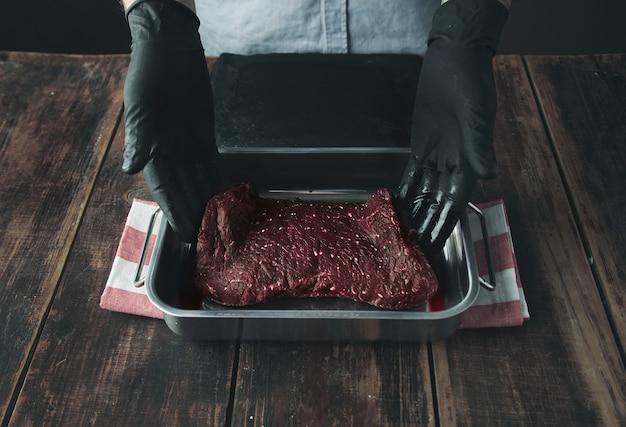 Getatoeëerde slagerhanden in zwarte handschoenen bieden stuk vers rauw vlees in kleurstof met sap of bloed voor de camera Gratis Foto