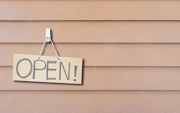 Getrokken uithangbord van het close-up bruin hard document met open bericht op bruine houten geweven muur Premium Foto