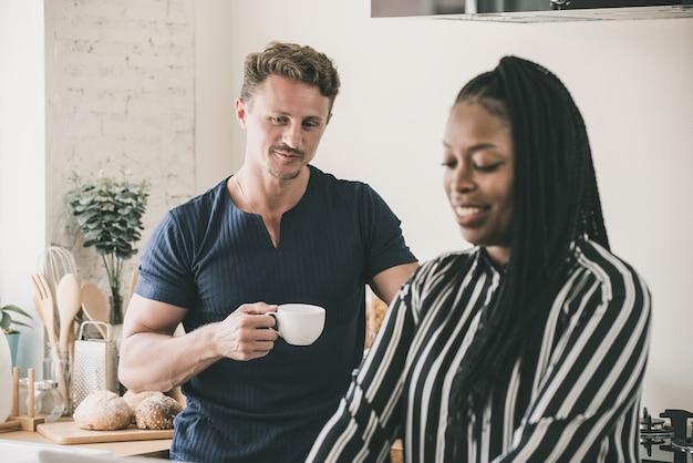 Getrouwd de routine van de levenochtend van interracial paar in de keuken Premium Foto
