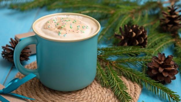 Geurige heerlijke koffie op een lichtblauwe tafel met dennentakken en kegels Premium Foto