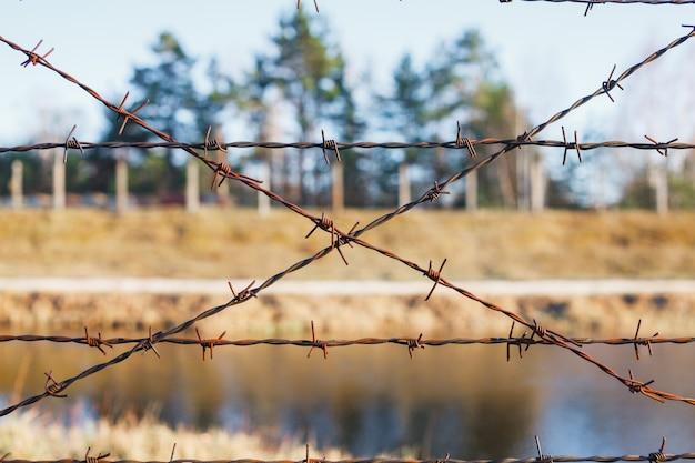 Gevaarlijk gebied omheind met prikkeldraadomheining Premium Foto