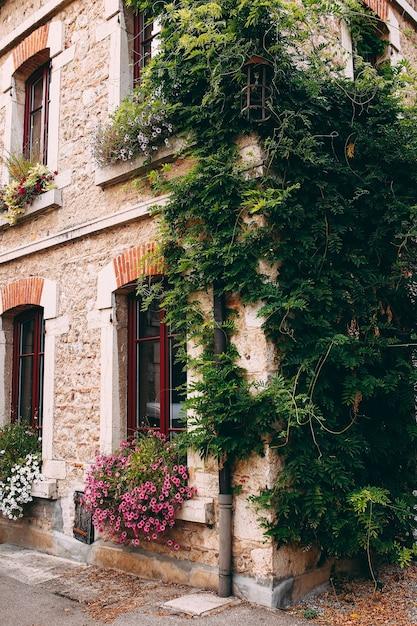 Gevel van oude stenen gebouwen in perouges, rode ramen, bloemen, frankrijk. hoge kwaliteit foto Premium Foto