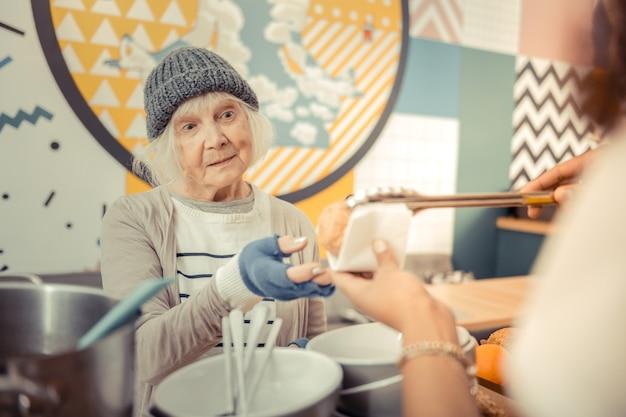Gevoel van honger. arme dakloze vrouw die naar het eten kijkt terwijl ze wil eten Premium Foto