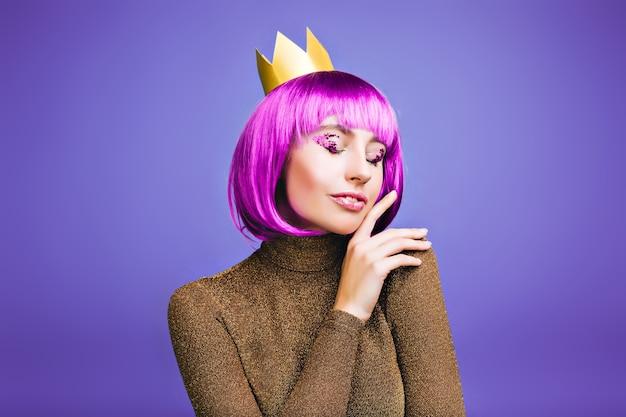 Gevoelig stijlvol portret van modieuze vrolijke jonge vrouw carnaval vieren in gouden kroon op violette ruimte. Gratis Foto