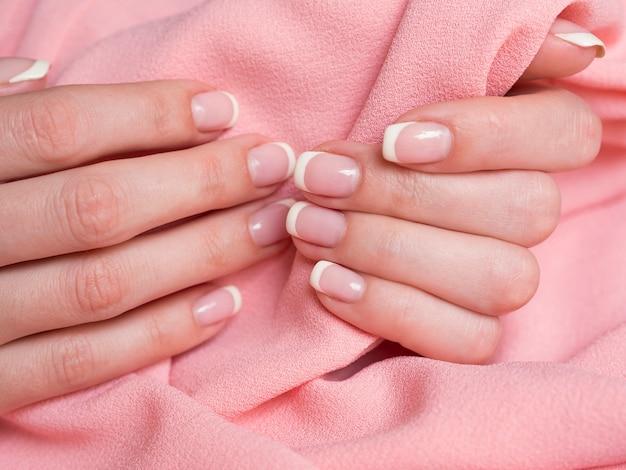 Gevoelige vrouwenhanden die roze stof houden Gratis Foto