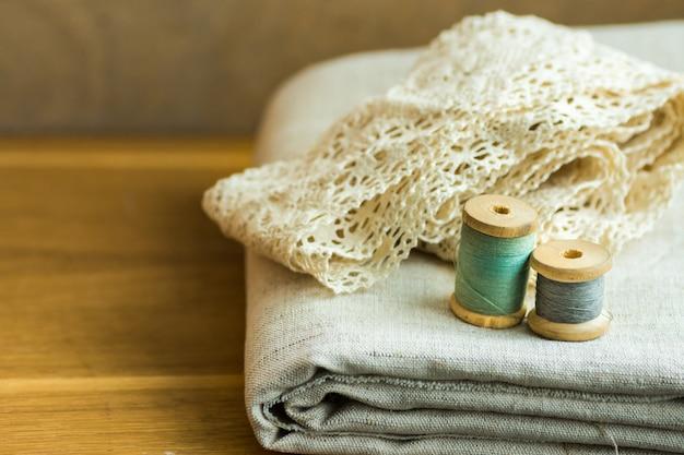 Gevouwen linnen stof, kant linten, draad houten spoelen op tafel Premium Foto