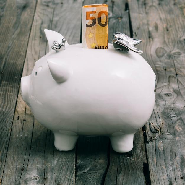 Gevouwen nota vijftig euro in de groef van witte piggybank op houten lijst Gratis Foto