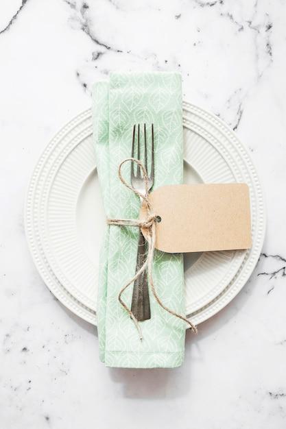 Gevouwen servet en vork vastgebonden met string en lege tag op witte keramische plaat Gratis Foto