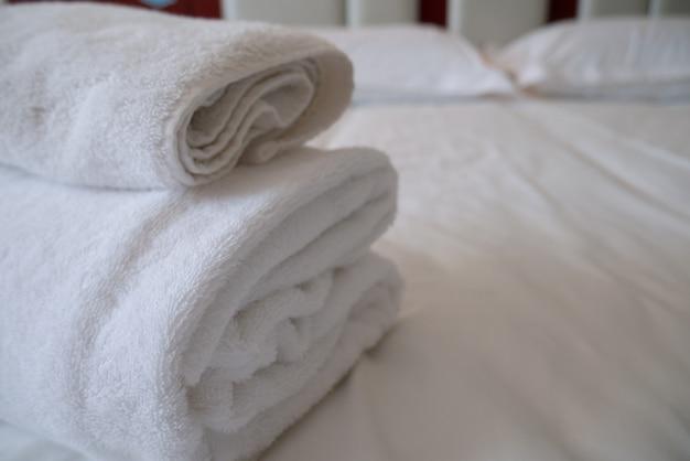 Gevouwen stapel witte handdoeken in hotelgastkamer voor comfortabele ontspanning Premium Foto
